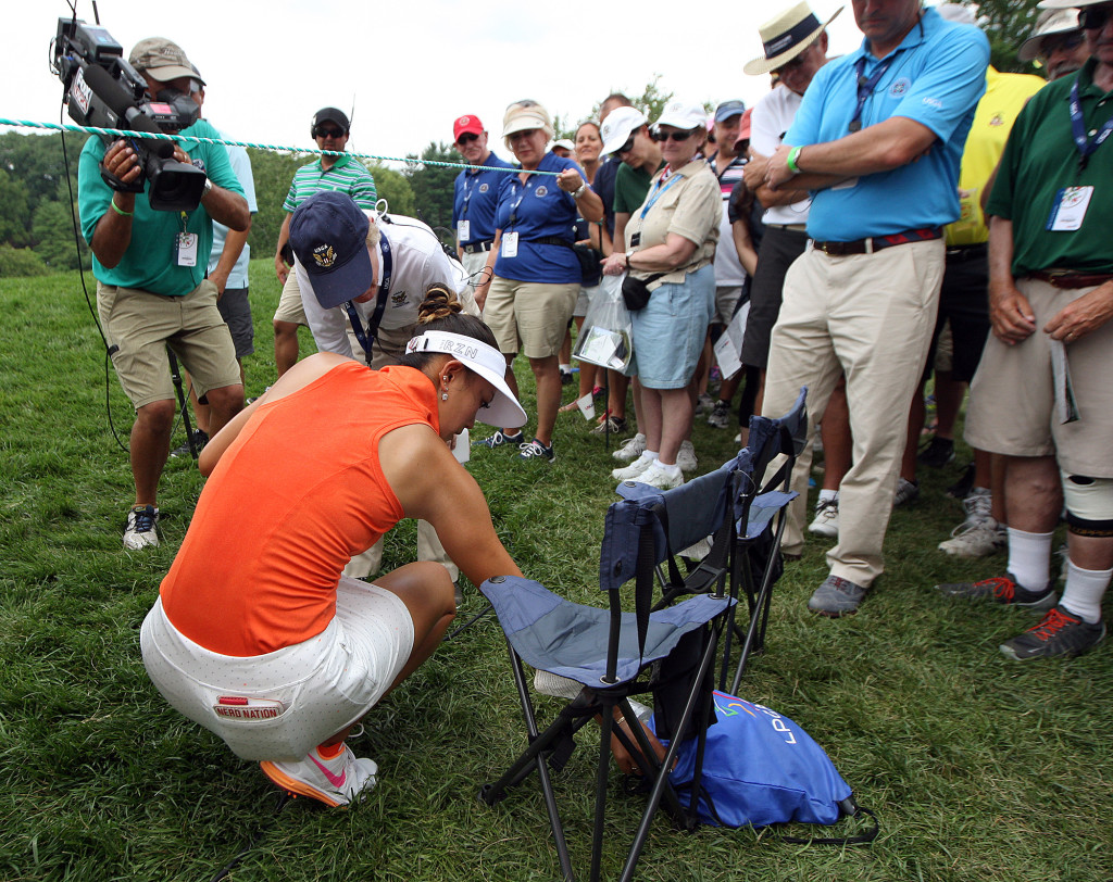 Michelle Wie, reaches into a fans bag to retrieve her ball after her tee shot on the 8th hole went into the gallery, during final day action of the 70th US Women's Open at Lancaster Country Club Sunday July 12, 2015. (Photo/Chris Knight)