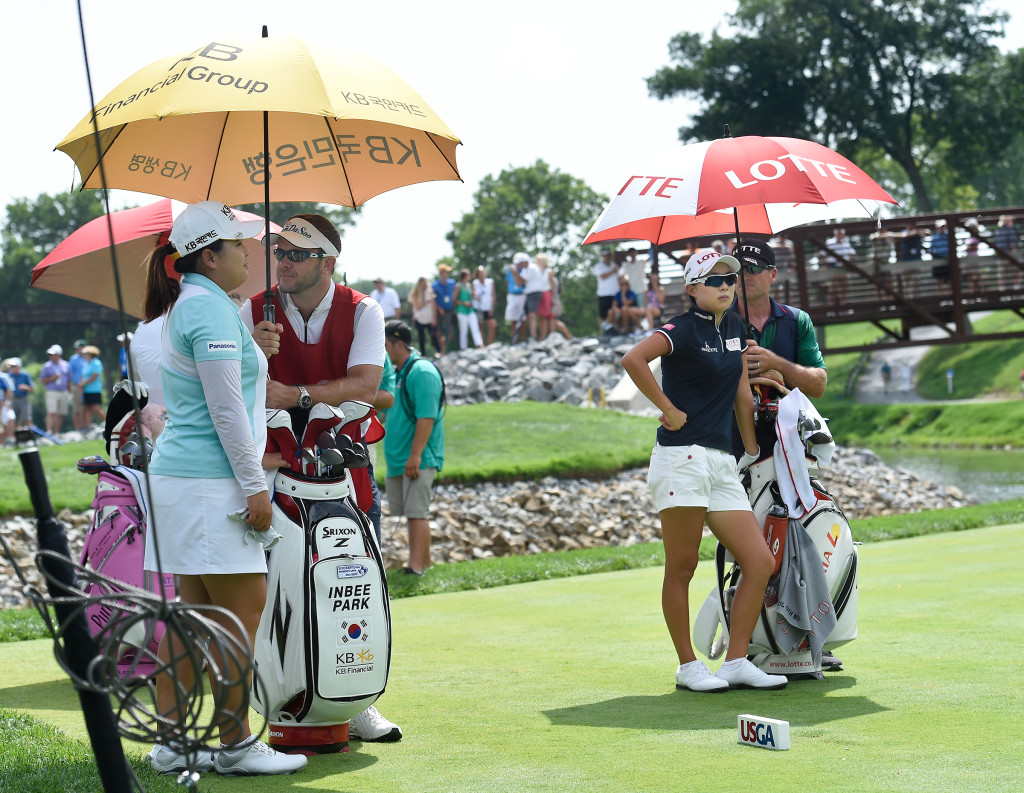 Inbee Park and Sei Young Kim and caddies, try to keep cool as the wait to hit their tee shots on number seven during the opening round of the US Women's Open at Lancaster Country Club on Thursday, July 9, 2015. (Photo/Suzette Wenger)